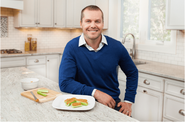 Man sitting at his kitchen counter preparing to eat a healthy meal.