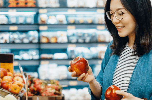 Woman choosing healthy food options at the grocery store.