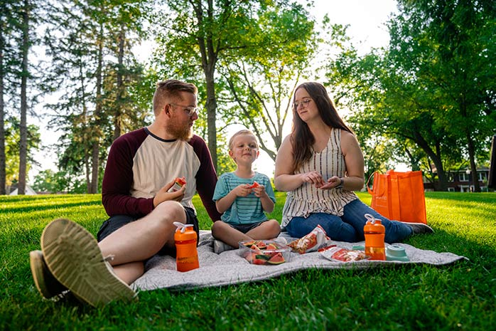 Photo of parents enjoying a picnic on a nice day in the park.