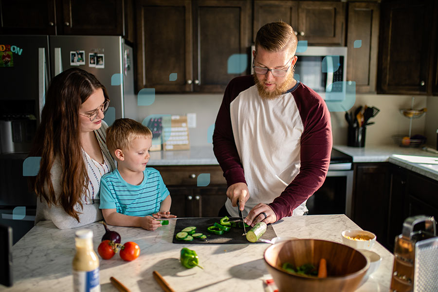 Young family cutting veggies together